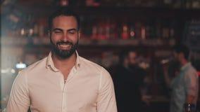 Portrait de l'homme attirant de sourire regardant la cam?ra dans un bar de barre ou de bi?re Concept de la jeunesse, de l'amiti?  banque de vidéos