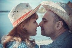 Portrait de l'homme avec la femme s'asseyant sur la plage et regardant à e Images stock
