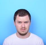 Portrait de l'homme avec le geste dusgusted sur le fond bleu Images stock