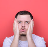Portrait de l'homme avec le geste dusgusted sur le fond rouge Photos libres de droits