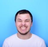 Portrait de l'homme avec le visage drôle sur le fond bleu Images stock