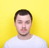 Portrait de l'homme avec le visage drôle sur le fond jaune Photographie stock libre de droits
