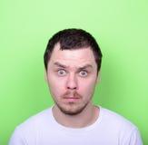 Portrait de l'homme avec le visage drôle sur le fond vert Photo stock
