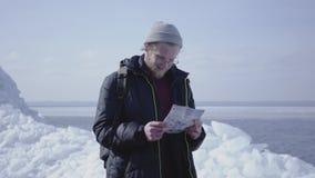 Portrait de l'homme bel barbu utilisant la veste chaude et le chapeau marchant sur le glacier vérifiant avec la carte stup?fier clips vidéos