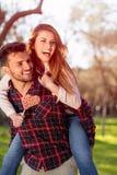 Portrait de l'homme bel de sourire donnant sur le dos à son amie dans la nature Image libre de droits