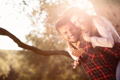 Portrait de l'homme bel de sourire donnant sur le dos à son amie dans la nature Image stock