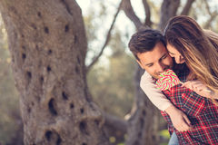 Portrait de l'homme bel de sourire donnant sur le dos à son amie dans la nature Photographie stock libre de droits
