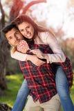Portrait de l'homme bel de sourire donnant sur le dos à son amie dans la nature Photographie stock