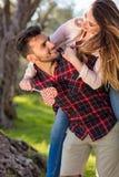 Portrait de l'homme bel de sourire donnant sur le dos à son amie dans la nature Images stock
