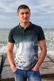 Portrait de l'homme caucasien aux cheveux foncés sérieux qui se tient sur un pilier Photographie stock libre de droits