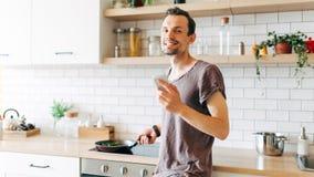 Portrait de l'homme châtain avec la poêle dans des ses mains parlant au téléphone dans la cuisine Photographie stock