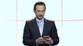 Portrait de l'homme d'affaires barbu mûr à l'aide du smartphone banque de vidéos