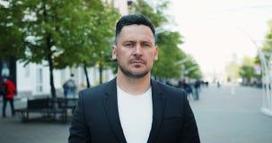Portrait de l'homme d'affaires d'homme bel se tenant dehors avec le visage sérieux banque de vidéos