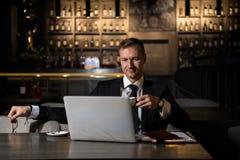 Portrait de l'homme d'affaires caucasien élégant bel s'asseyant au restaurant travaillant à son ordinateur portable et café potab image libre de droits