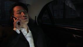 Portrait de l'homme d'affaires coréen qui parle sur le smartphone dans le taxi confortable foncé banque de vidéos