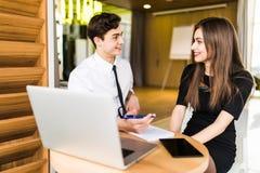 Portrait de l'homme d'affaires de conseiller en investissement s'asseyant au bureau devant l'ordinateur et consultant la femme pr photos stock