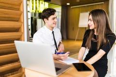 Portrait de l'homme d'affaires de conseiller en investissement s'asseyant au bureau devant l'ordinateur et consultant la femme pr photo stock