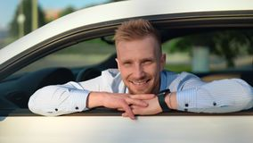Portrait de l'homme d'affaires masculin bel posant à la voiture de sport de luxe blanche regardant par la fenêtre ouverte clips vidéos
