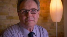 Portrait de l'homme d'affaires supérieur dans la chemise observant dans la caméra avec le sourire modeste et calme banque de vidéos