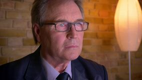 Portrait de l'homme d'affaires supérieur en costume et verres observant des nouvelles à la TV étant sérieuse et concentrée clips vidéos