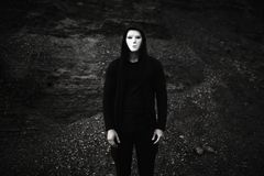 Portrait de l'homme dans le masque anonyme blanc de port de hoodie noir photographie stock