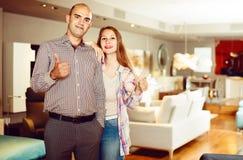 Portrait de l'homme et de femme avec des pouces dans le salon de meubles image libre de droits