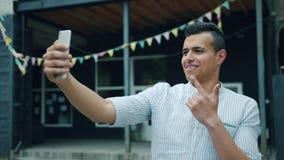 Portrait de l'homme joyeux de métis prenant le selfie dehors utilisant la caméra de smartphone banque de vidéos