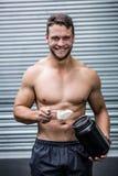 Portrait de l'homme musculaire de sourire faisant le cocktail de protéine image libre de droits