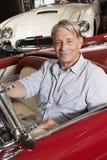 Portrait de l'homme plus âgé de sourire s'asseyant dans la voiture dans la boutique Photographie stock libre de droits