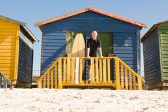 Portrait de l'homme se tenant avec la planche de surf à la hutte de plage Photographie stock libre de droits