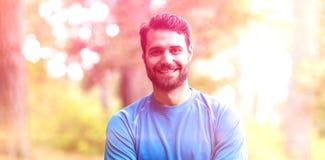 Portrait de l'homme se tenant dans la forêt avec des bras croisés Images stock