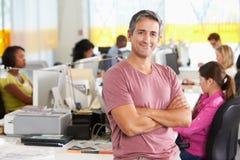Portrait de l'homme se tenant dans le bureau créatif occupé Photographie stock libre de droits