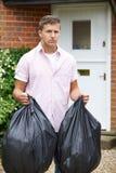 Portrait de l'homme sortant des déchets dans les sacs Photographie stock libre de droits