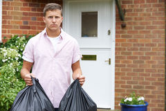 Portrait de l'homme sortant des déchets dans les sacs image stock