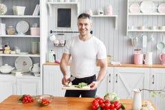 Portrait de l'homme de sourire bel coupant des légumes dans la cuisine Le concept des produits qui respecte l'environnement pour  image libre de droits