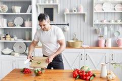 Portrait de l'homme de sourire bel coupant des légumes dans la cuisine Le concept des produits qui respecte l'environnement pour  image stock