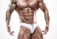 Portrait de l'homme sportif fort de forme physique montrant de grands muscles photos stock