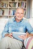 Portrait de l'homme supérieur à l'aide du comprimé tout en se reposant sur le sofa Photographie stock