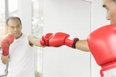 Portrait de l'homme supérieur asiatique de combattant poinçonnant avec le gl rouge de boxe Photo libre de droits