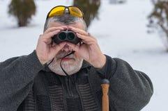 Portrait de l'homme supérieur caucasien barbu regardant par des jumelles la saison d'hiver Photos libres de droits