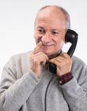 Portrait de l'homme supérieur heureux parlant au vieux téléphone de ligne terrestre photo libre de droits