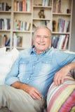 Portrait de l'homme supérieur heureux s'asseyant sur le sofa Photo libre de droits