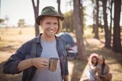 Portrait de l'homme tenant la tasse tout en se tenant contre des amis Photo libre de droits