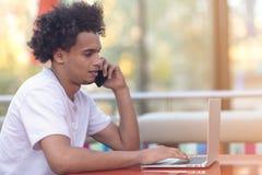 Portrait de l'homme travaillant sur l'ordinateur portable au téléphone images libres de droits