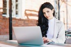 Portrait de l'indépendant féminin de belle brune dactylographiant un messag photos stock