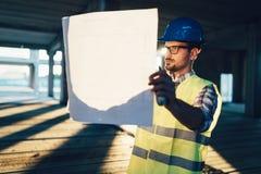 Portrait de l'ingénieur masculin d'entrepreneur de site avec le casque antichoc tenant le papier de croquis de mise au point photographie stock libre de droits