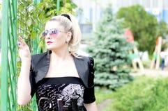 Portrait de la belle femme à une grille de fer, contre le parc Image libre de droits