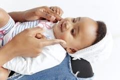 Portrait de la belle femme africaine tenant sur des mains son peu de bébé photographie stock