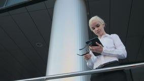 Portrait de la belle femme d'affaires à l'aide de la tablette en dehors du centre Photographie stock