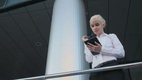 Portrait de la belle femme d'affaires à l'aide de la tablette en dehors du centre Image stock